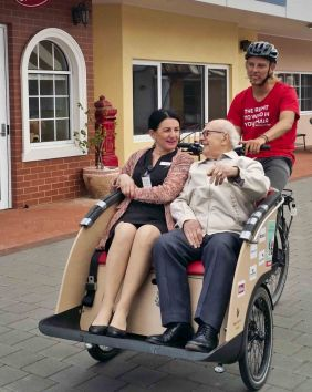 Carer and resident share a bike ride